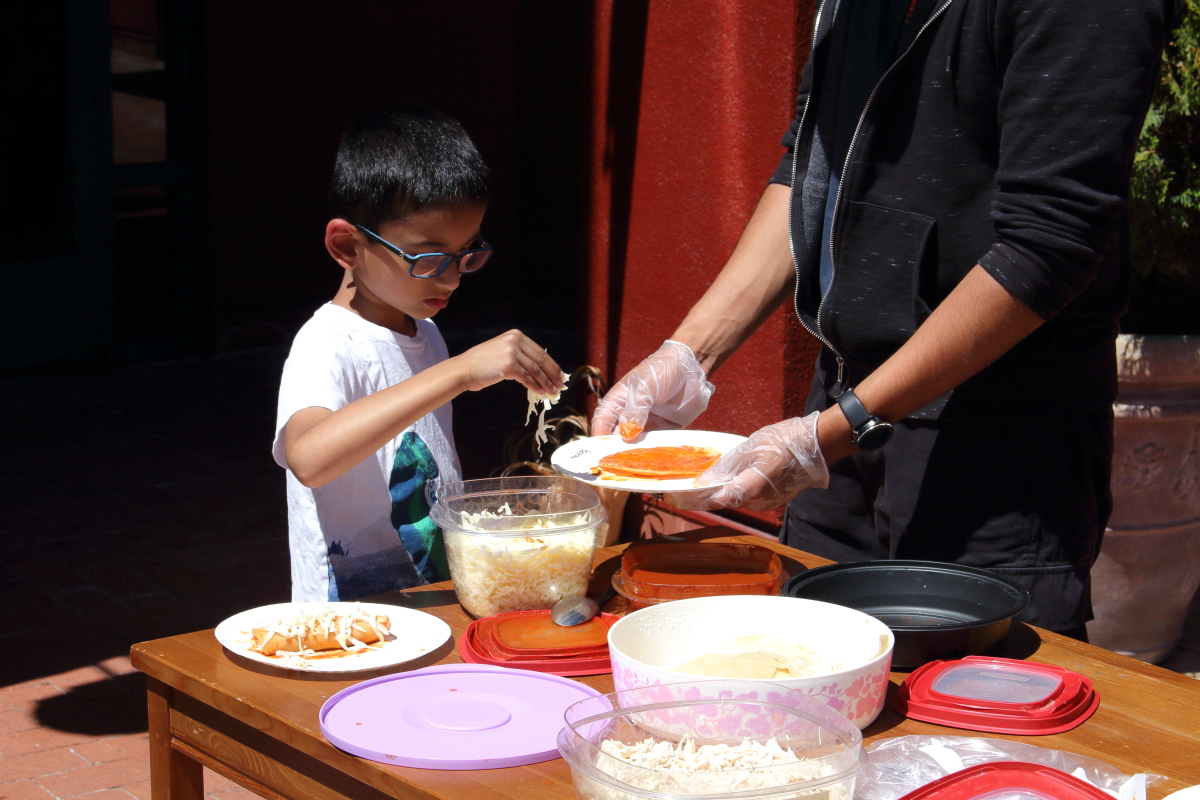 Our summer camp students learn to make enchilada in a cooking lesson.