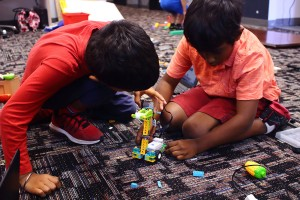 Summer camp students work in teams to build and program their LEGO® robotics projects.